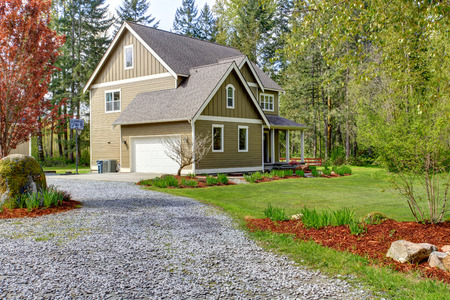 Countryside house exterior with garage. View of entrance and gravel driveway