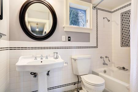 Bright bathroom interior with tile wall trim, white bath tub, toilet and washbasin cabinet