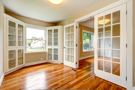 Emtpy house with new hardwood floor and white french doors. View of entrance hallway and small office room