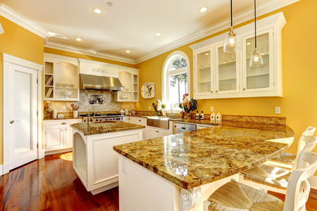 Bright yellow kitchen interior in luxury house with granite tops and kitchen island.