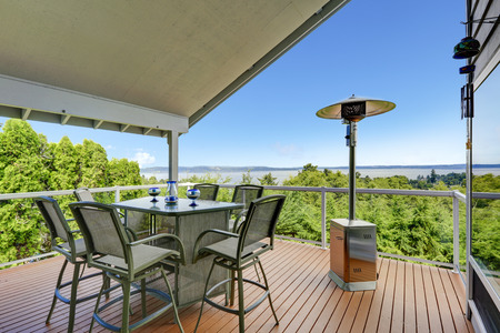 Patio area with table, chairs and heater on walkout deck overlooking scenic view