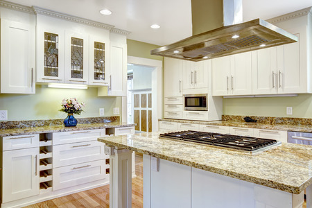 Modern and practical kitchen room design. White cabinet with granite tops, kitchen island with built-in stove and steel hood