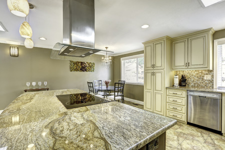 Spacious kitchen room with tile floor. Big kitchen island with built-in stove, granite top and steel hood