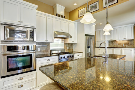 Bright kitchen room with granite tops, kitchen island and white cabinets