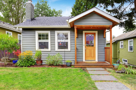 Foto de Small grey house with wooden deck. Front yard with flower bed and lawn - Imagen libre de derechos