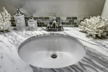 Modern bathroom vanity cabinet with white granite top. Sink view. White sink with steel faucet and decorated corals