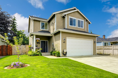 Two story house exterior with white door garage and driveway