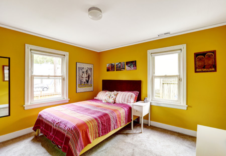 Bedroom in bright yellow color with single bed. Red stripped bedding