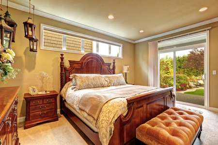 Luxury bedroom with carved wood bed, nightstand, ottoman and decorative lanterns. Room has exit to backyar area