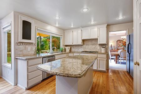 Kitchen room with white storage combination. Kitchen island with granite top