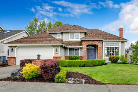 Photo pour Classic house exterior with brick trimmed entrance porch, green lawn and trimmed hedges. Garage with driveway - image libre de droit
