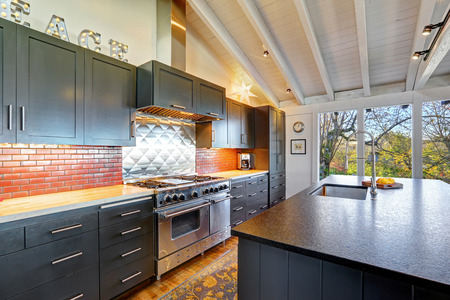 Luxury beautiful dark modern kitchen with vaulted wood ceiling, hardwood floor and huge stove.