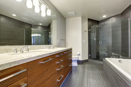 Beautifully modernized bathroom with gray flooring and large glass shower.