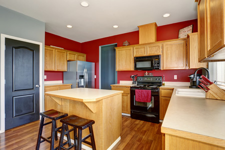Small kitchen with island, also red and gray walls.