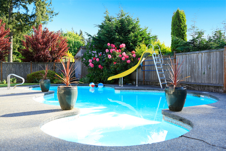 Photo pour Fenced backyard with small beautiful swimming pool and playground - image libre de droit