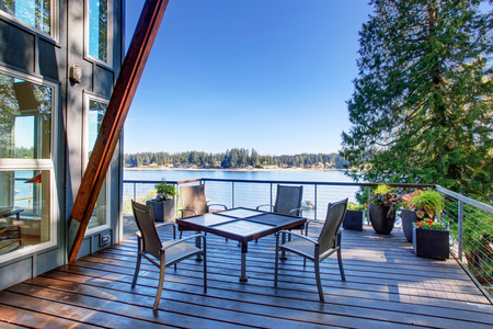 Foto de Large covered and furnished porch of luxury house with view of the lake. House exterior. - Imagen libre de derechos