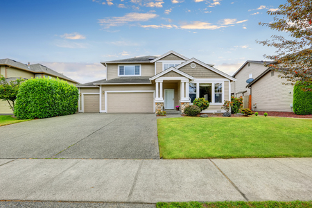 Photo for Neat beige home with two garage spaces and large concrete driveway. Northwest, USA - Royalty Free Image