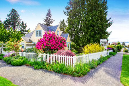 Photo for Small Yellow house exterior with White picket fence and Decorative Gate. Northwest,USA - Royalty Free Image