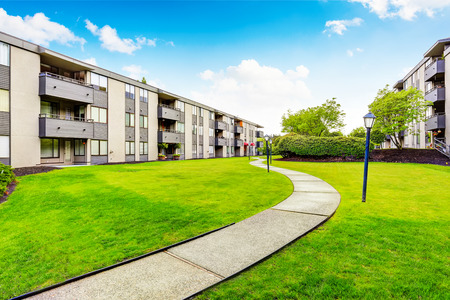 Foto de Large beige apartment building with three floors and balconies. Well kept lawn. Northwest, USA. - Imagen libre de derechos