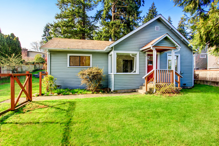 Foto de Small grey house with wooden deck. Front yard with flower bed and lawn. Northwest, USA - Imagen libre de derechos