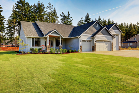 Photo for Luxury blue house with curb appeal. Three car garage with driveway . And freshly mowed garden lawn. Northwest, USA - Royalty Free Image