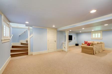 Photo pour Spacious basement room interior in pastel blue tones. Beige carpet floor and large corner sofa with TV. Northwest, USA - image libre de droit