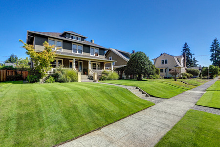 Nice curb appeal of American craftsman style house. Column porch view and freshly mowed garden lawn. Northwest, USA