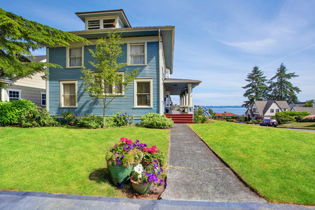Classic large craftsman old American house exterior in blue tones with well kept garden and perfect water view. Northwest, USA.の写真素材