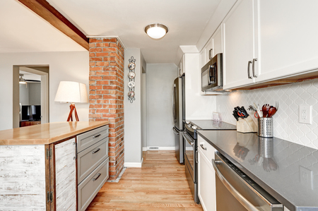White kitchen room interior with grey details. White backsplash , glossy counters , small kitchen island designed in old style and red brick accent wall . Northwest, USAの写真素材