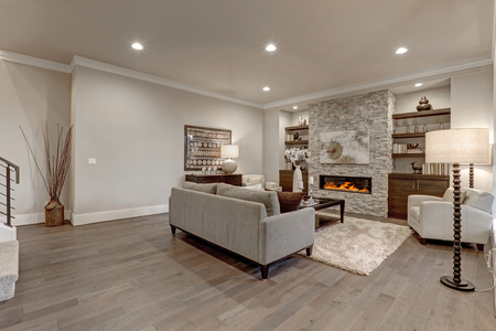 Photo pour Living room interior in gray and brown colors features gray sofa atop dark hardwood floors facing stone fireplace with built-in shelves. Northwest, USA  - image libre de droit