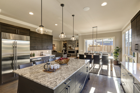 Modern gray kitchen features  dark gray cabinetry paired with white quartz countertops and a glossy gray linear tile backsplash. Bar style kitchen island with granite counter. Northwest, USA