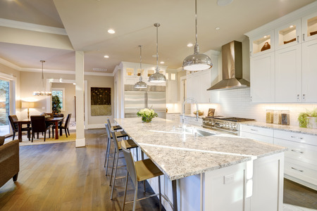 Photo pour White kitchen design features large bar style kitchen island with granite countertop illuminated by modern pendant lights. Northwest, USA - image libre de droit