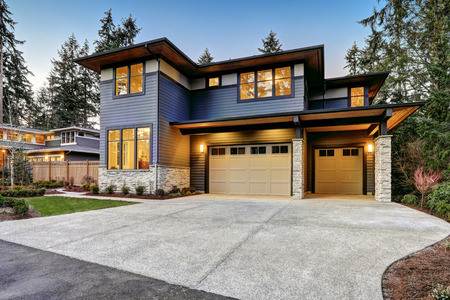 Photo pour Luxurious new construction home in Bellevue, WA. Modern style home boasts two car garage framed by blue siding and natural stone wall trim. Northwest, USA - image libre de droit