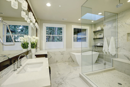 Foto de Amazing white and gray marble master bathroom with large glass walk-in shower, freestanding tub and skylights on the ceiling. Northwest, USA - Imagen libre de derechos