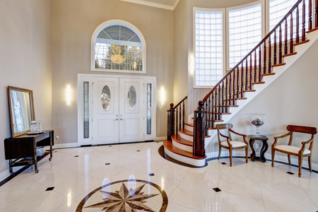 Photo pour Stunning two story entry foyer with lots of space boasts marble mosaic tile floor, front door framed with arch window and sidelights, grand staircase with glossy wood curved banister. Northwest, USA - image libre de droit