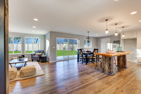 Photo for Open floor plan interior with polished hardwood floors showcases an impressive reclaimed wood kitchen island, black dining table set and sliding doors to fenced backyard. Northwest, USA - Royalty Free Image