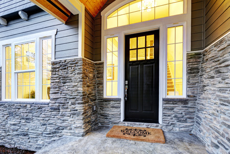 Foto de Front covered porch design boasts stone siding which creates immense curb appeal of luxurious home. Welcome mat lead to black front door accented with sidelights framed by white siding. Northwest, USA - Imagen libre de derechos