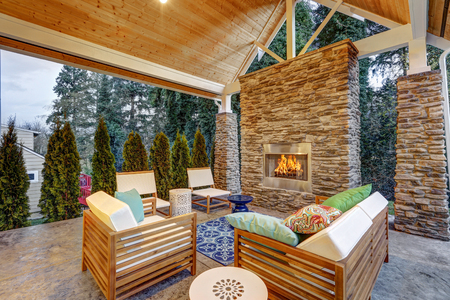 Foto de Chic covered back patio with built in gas fireplace, stone pillars, plank vaulted ceiling over cozy teak wood sofa set topped with white cushions and green pillows. Northwest, USA  - Imagen libre de derechos