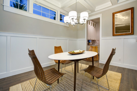Lovely craftsman style dining room with coffered cealing over modern oval dining table surrounded by bentwood chairs atop sisal rug. Northwest, USA