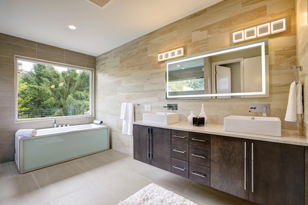 Photo pour Contemporary master bathroom features a dark vanity cabinet fitted with rectangular his and hers sink and modern wall mount faucets, also modern tub by the window. Northwest, USA - image libre de droit