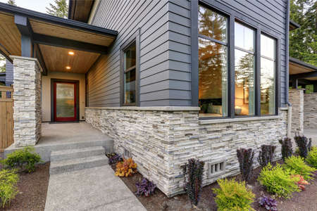 Photo for Luxurious new home with curb appeal. Trendy grey two-story exterior in Bellevue with large picture windows, stone siding, covered porch and concrete pathway. Northwest, USA - Royalty Free Image