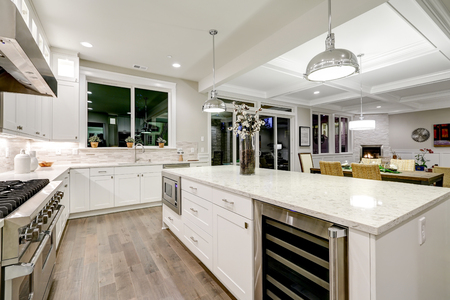 Photo for Gourmet kitchen features white shaker cabinets with marble countertops, stone subway tile backsplash and gorgeous kitchen island. Northwest, USA - Royalty Free Image