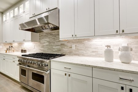 Foto de Gourmet kitchen features white shaker cabinets with marble countertops paired with stone subway tile backsplash and stainless steel hood over eight burner gas range. Northwest, USA - Imagen libre de derechos