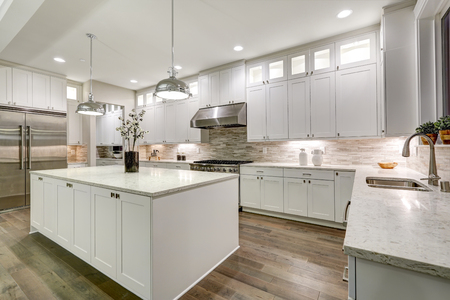 Photo for Gourmet kitchen features white shaker cabinets with marble countertops, stone subway tile backsplash, double door stainless steel refrigerator and gorgeous kitchen island. Northwest, USA - Royalty Free Image