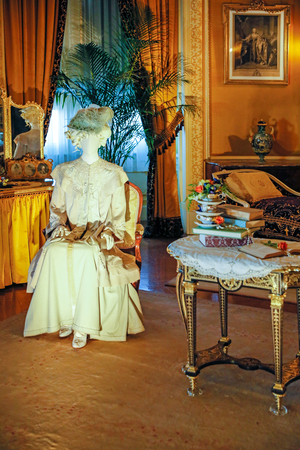ASHEVILLE, NORTH CAROLINA - MARCH 4, 2017: Biltmore's costume exhibition. The House of Mirth is featured in Mrs Vanderbilt's bedroom. Costumes were arranged with mirrors to see the backs of both.