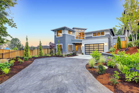 Photo pour Excellent curb appeal of a Modern craftsman style home accented by landscaping, garage with glass door and long asphalt driveway. Northwest, USA - image libre de droit