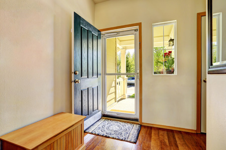 Photo pour Small foyer with green open front door, laminate floor and wooden bench. Northwest, USA - image libre de droit