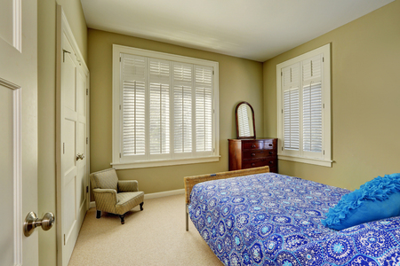 Photo pour Green olive bedroom interior with blue bed, wood cabinet with drawers,  windows dressed in plantation shutters and walk-in closet. Northwest, USA - image libre de droit