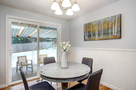 Photo pour Breakfast nook with round white washed table and glass doors to back patio. - image libre de droit