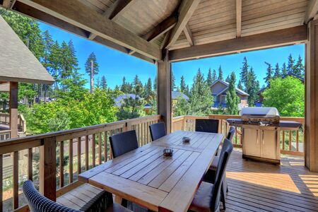 Photo pour Beautiful covered deck with large luxury dining room table with grill and railings. Lots of pine trees. - image libre de droit